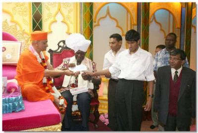The Vice President accepts a cheque from Acharya Swamishree and disciples