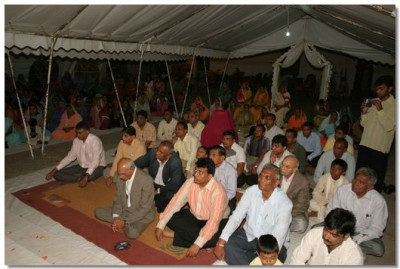 Disciples attentively listen to Acharya Swamishree's divine blessings