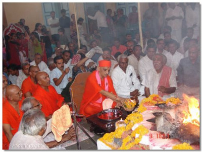 Acharya Swamishree offers a coconut and flowers to the fire