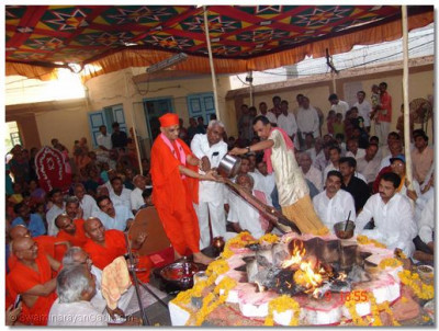 Acharya Swamishree pours ghee into the fire
