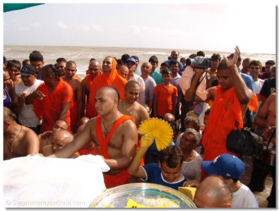 Sants and disciples wade in the ocean water, trying to get a glimpse of the Lord's divine darshan