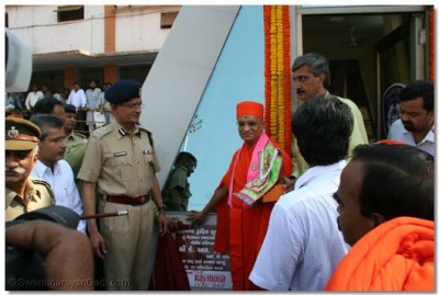 Acharya Swamishree unveils a plaque to officially declare the opening of the police sub-station.