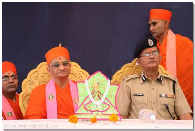 Acharya Swamishree gives darshan during the special assembly held during the opening with Ahmedabad's Police Commissioner, Shree K R Kaushik