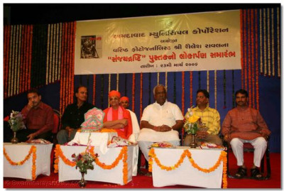 Acharya Swamishree and invited guests seated on the stage