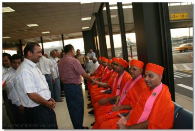 Devotees greet the sants in the airport arrival lounge
