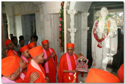 Sants perform aarti to the Murti of Jeevanpran Swamibapa and Acharya Swamishree who gives darshan at the entrance of Smruti Mandir