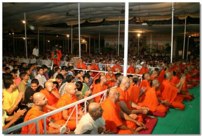 Acharya Swamishree, sants, and devotees watch the evening performances