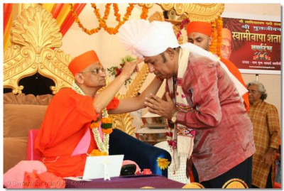 Acharya Swamishree honours Shree Upendra Trivedi with a prasad pagh and chandlo
