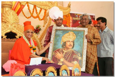 Acharya Swamishree presents a portrait to Shree Upendra Trivedi