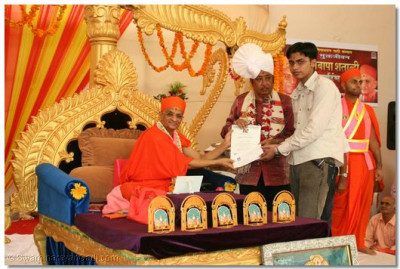Acharya Swamishree and Shree Upendra Trivedi presents an award to a student