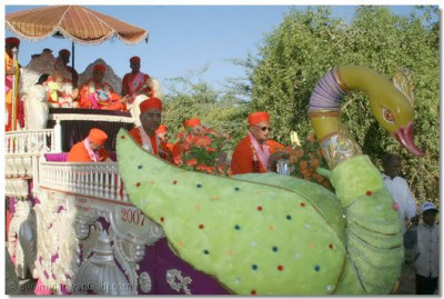 Jeevanpran Swamibapa, Acharya Swamishree, and sants give darshan seated on a float during the start of the procession