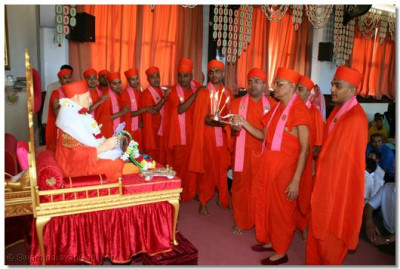 Acharya Swamishree and sants perform aarti to Jeevanpran Swamibapa