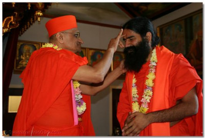 Acharya Swamishree honours Swami Ramdevji by impressing a chandlo on him
