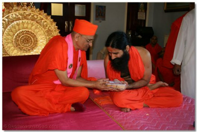 Acharya Swamishree blesses Swami Ramdevji with an offering of prasad