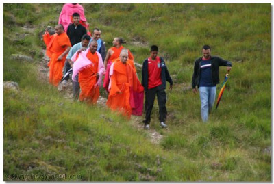 Sants and disciples try to keep up with Acharya Swamishree during the decent down the mountain
