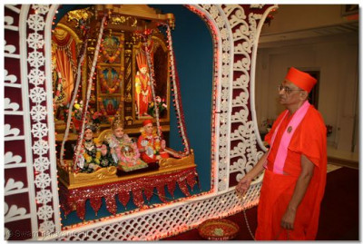 Acharya Swamishree gently swings Lord Swaminarayan, Jeevanpran Bapashree, and Jeevanpran Swamibapa