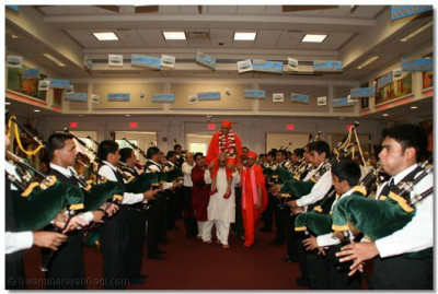 Acharya Swamishree is carried into the temple through a Guard of Honour formed by Shree Swamibapa Pipe Band