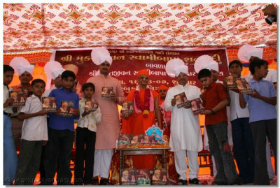Acharya Swamishree, the Minister, honourable guests distribute notebooks to the school children of Bavla