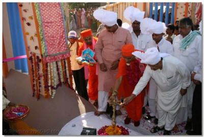 Acharya Swamishree and the Minister light the auspicious flame before the gate opening