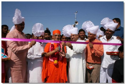 Acharya Swamishree and the Minister cut the ribbon to mark the opening of the gate