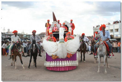 Acharya Swamishree's chariot is flanked by men on horseback