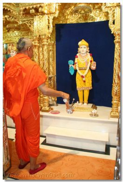 Acharya Swamishree performs aarti to Lord Swaminarayan