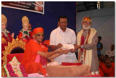 Acharya Swamishree presents an award to one of the lecturers at Shree Swaminarayan Arts College