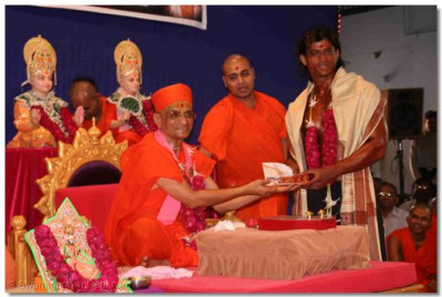 On behalf of Shree Swaminarayan Gadi Sansthan, Acharya Swamishree presents a scholarship to the young body builder