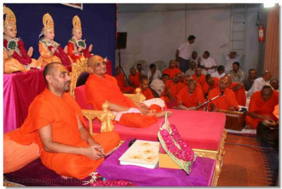 Acharya Swamishree gives darshan whilst the aarti ceremony takes place. Beside Acharya Swamishree is seated Shree Vignanprakashdasji Swami, the sant who recited the discourses