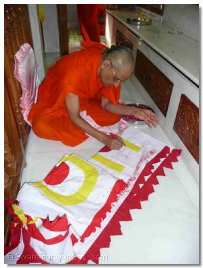 Acharya Swamishree consecrates the flag that was to be hung from the topmost dome of the temple