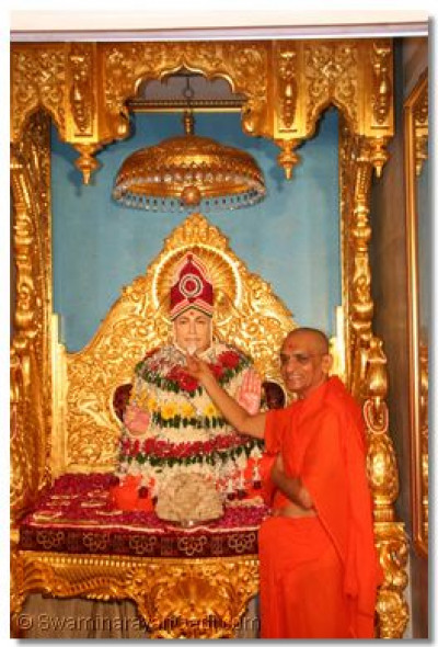 Acharya Swamishree offers thaar to Jeevanpran Swamibapa during the opening ceremony of the new gold sinhasan