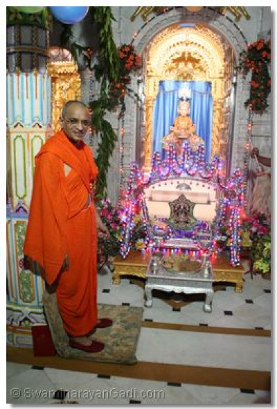 Acharya Swamishree gives darshan with Shree Harikrishna Maharaj seated on a swing