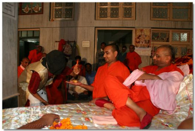 Acharya Swamishree watches as the magician performs a trick with a sant