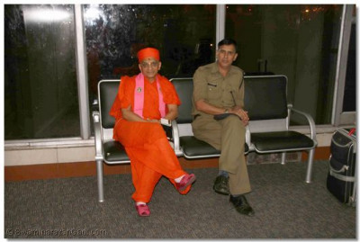 Acharya Swamishree waits for the plane in Mumbai with the Airport Chief Security Officer