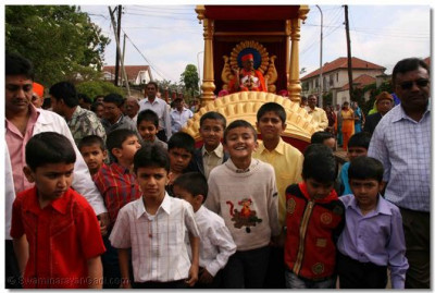 Young disciples pull the chariot upon which Acharya Swamishree presides