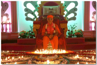 Acharya Swamishree presides amongst the spectacular arrangement of flowers and candles