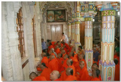 Sants and disciple seated inside the temple for the darshan of Acharya Swamishree performing panchamrut snan