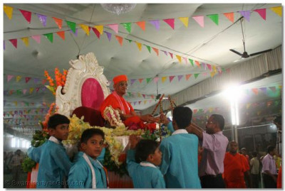 Acharya Swamishree lovingly plays dandia with the young disciples
