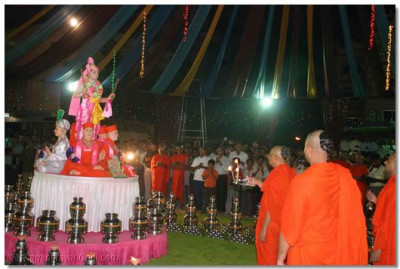 Acharya Swamishree performs aarti to the Lord at the end of the Sharad Poonam festivities