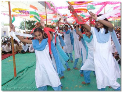 Young girls from a nearby school perform a patriotic dance