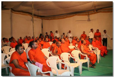 Acharya Swamishree and sants watch a video presentation - documentary about Jeevanpran Swamibapa