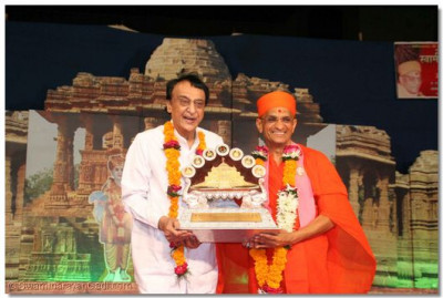 Acharya Swamishree presents a memento to the famous magician Shree Kelal