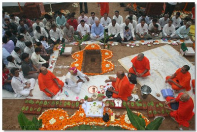 Sants and disciples perform the Mahapooja ceremony at the site where the foundation stone was placed