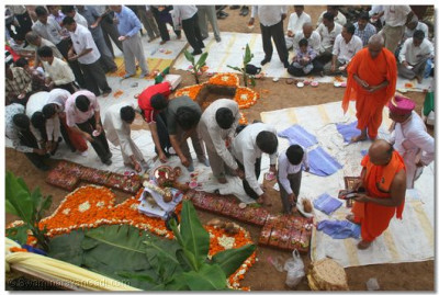 Disciples sprinkle auspicious kanku and flowers on the ceremonial bricks to be placed in the foundations