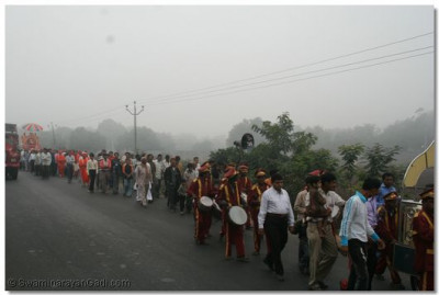 The procession proceeds towards the new Temple site