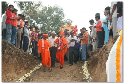 Acharya Swamishree walks down to the site of the Temple foundations