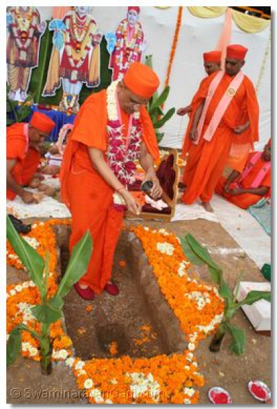 Acharya Swamishree sprinkles holy water into the cavity where the Foundation Stone is to be placed