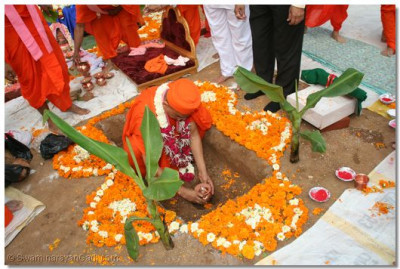 Acharya Swamishree places the ceremonial urn into the Temple Foundations