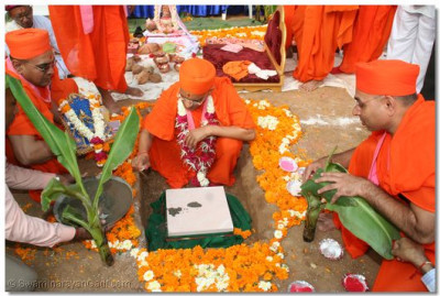 Acharya Swamishree places the Foundation Stone into the ground