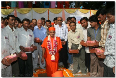 Disciples hand their ceremonial bricks to Acharya Swamishree, to place into the new Temple Foundations